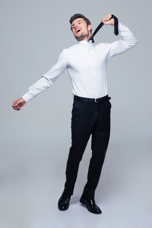 Full length portrait of a happy young businessman to hang himself with tie over gray background photo