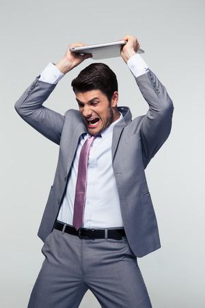 smashing: Angry businessman smashing his laptop over gray background