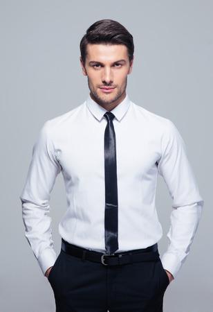 灰色の背景の上のポケットの手で立っている青年実業家