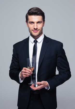 champagne: Happy businessman holding glass of champagne over gray background and looking at camera