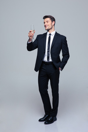Full length portrait of a smiling businessman holding glass of champagne over gray background and looking at camera