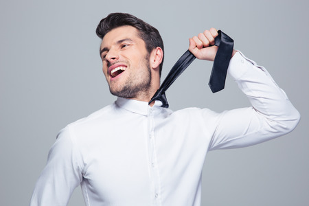 Happy businessman to hang himself with tie over gray background photo
