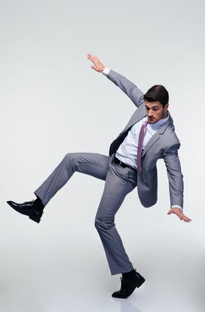 Knappe zakenman vliegen over grijze achtergrond en op zoek naar beneden