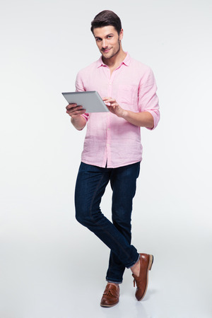 灰色の背景の上にタブレット コンピューターを使用してカメラを見て若い男の完全な長さの肖像画 写真素材