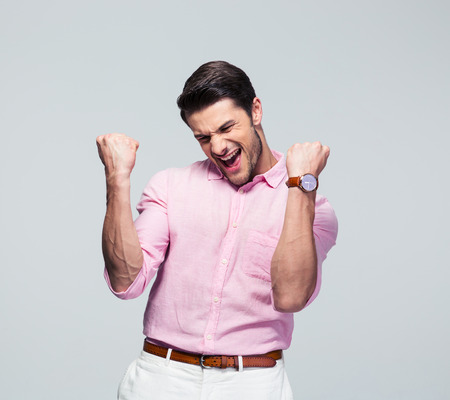 Happy young man celebrating his success over gray background Stock Photo