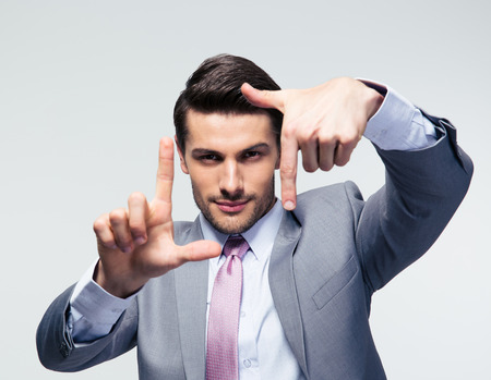 patron: Hombre de negocios haciendo gesto del marco sobre fondo gris y mirando a cámara
