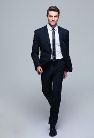 灰色の背景の上ファッション男性モデルの完全な長さの肖像画。カメラを目線 写真素材