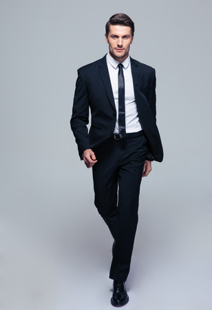 Full length portrait of a fashion male model over gray background. Looking at camera