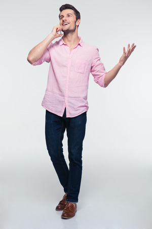 talking: Full length portrait of a young happy man talking on the phone over gray background. Wearing in shirt and jeans Stock Photo