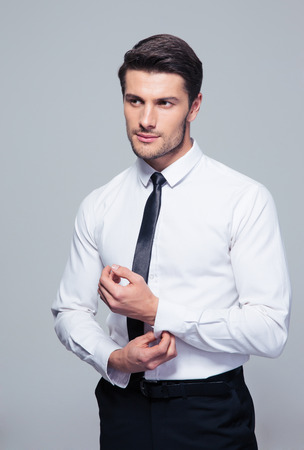 buttoning: Handsome businessman buttoning shirt over gray background Stock Photo