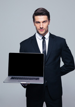 businessman smiling: Confident businessman showing blank laptop screen over gray background. Looking at camera