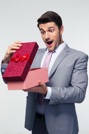 Knappe zakenman opening geschenk doos over de grijze achtergrond Stockfoto