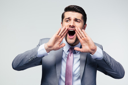displeased businessman: Handsome businessman shouting over gray background and looking away