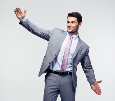 handsign: Businessman bragging about the size of something over gray background