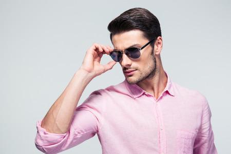 bel homme: Beau jeune homme en lunettes de soleil et chemise sur fond gris