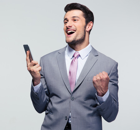 businessman smiling: Cheerful businessman holding smartphone and celebrating his success over gray background