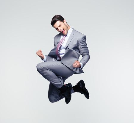 bel homme: D'affaires gaie dr�le de sauter dans l'air sur fond gris Banque d'images