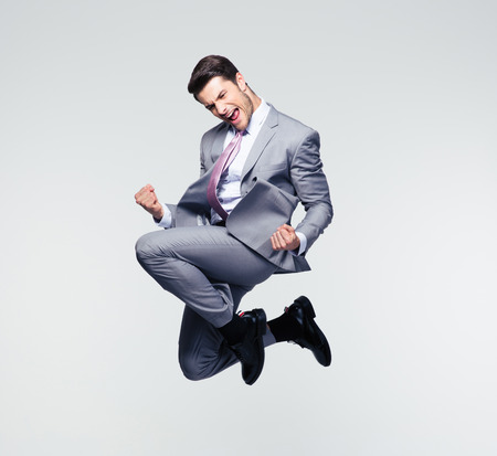 Funny cheerful businessman jumping in air over gray background