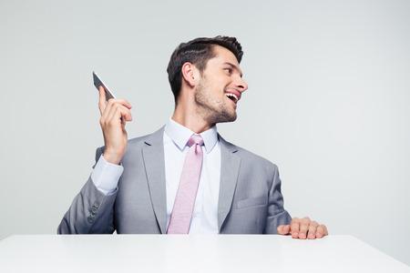 personas mirando: Hombre de negocios sentado en la mesa con el teléfono inteligente y que mira lejos sobre fondo gris