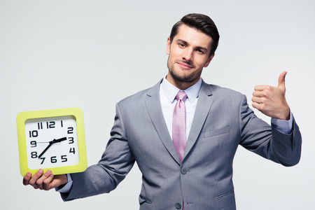 great job: Businessman holding clock and showing thumb up over gray background