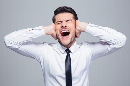 Zakenman die zijn oren en schreeuwen over grijze achtergrond Stockfoto