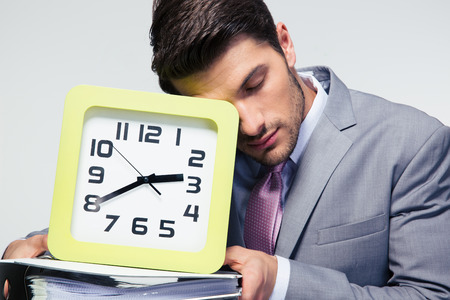 sleeping businessman: Portrait of a sleeping businessman holding folders and clock over gray background