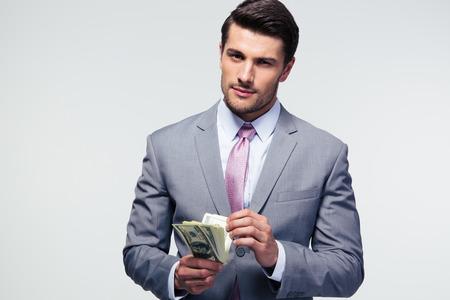 cuenta: Apuesto hombre de negocios contando dólares estadounidenses sobre fondo gris y mirando a cámara Foto de archivo