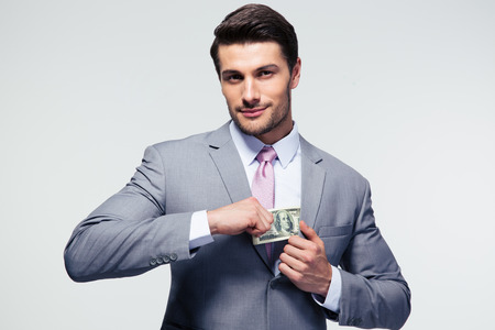 putting money in pocket: Businessman putting money in pocket over gray background. Looking at camera
