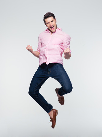 Businessman celebrating his success and jumping over gray background. Looking at camera Banque d'images