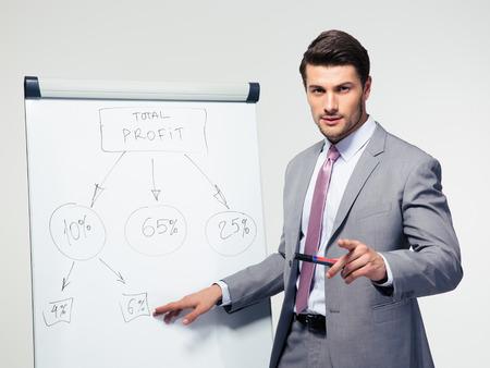 Handsome Geschäftsmann macht Präsentation auf Flipchart auf grauem Hintergrund. Blick in die Kamera