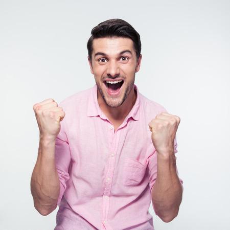 celebra: Hombre de negocios feliz que celebra su éxito sobre fondo gris. Mirando a la cámara Foto de archivo