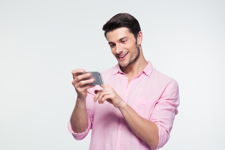 cell phone addiction: Happy businessman using smartphone over gray background Stock Photo