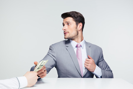 venality: Businessman sitting at the table and taking bribe over gray background. Looking away