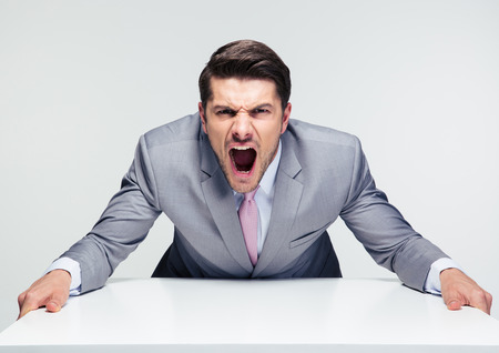 angry businessman: Angry businessman sitting at the table and screaming over gray background. Looking at camera
