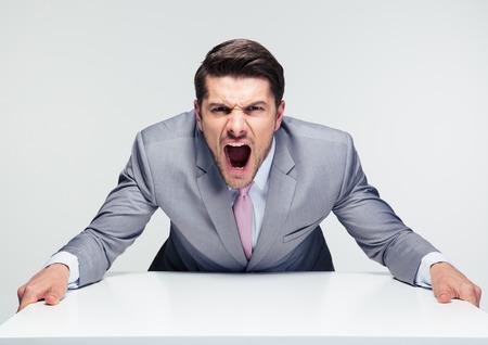 enojo: Hombre de negocios enojado que se sienta a la mesa y gritando sobre fondo gris. Mirando a la cámara