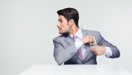 certitude: Young businessman sitting at the table and putting money in pocket over gray background. Looking away Stock Photo