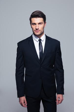 Pohledný mladý podnikatel, stojící nad šedé pozadí a při pohledu na fotoaparát