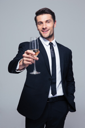 Happy businessman holding glass of champagne over gray background and looking at camera