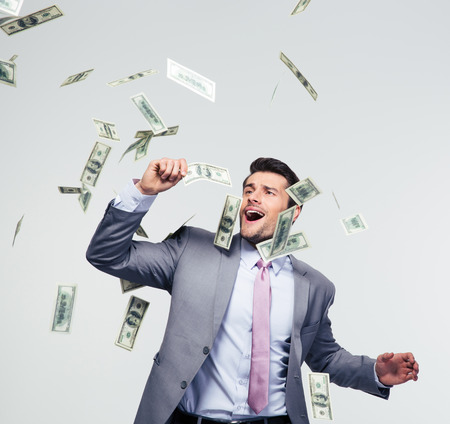 Businessman standing under money rain over gray background