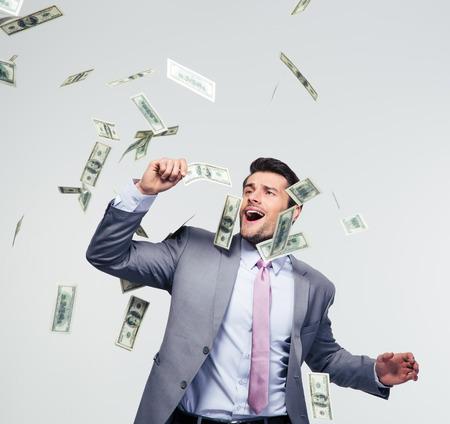 hombre cayendo: Empresario de pie bajo la lluvia de dinero sobre fondo gris Foto de archivo