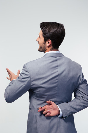 unethical: Back view portrait of a businessman with fingers crossed over gray background Stock Photo