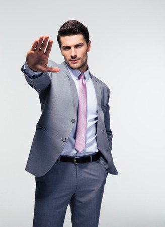 man power: Businessman showing stop gesture over gray background. Looking at camera