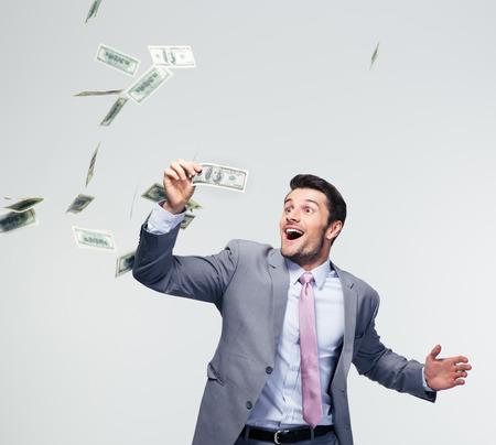 cash money: Empresario de pie bajo la lluvia de dinero sobre fondo gris Foto de archivo