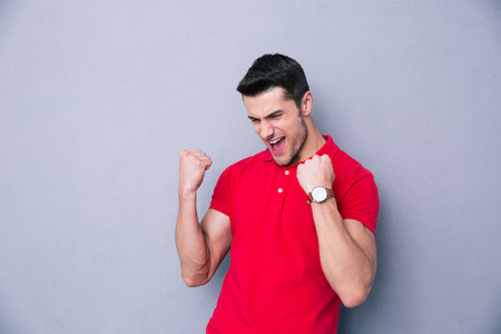 Casual man vieren succes over grijze achtergrond