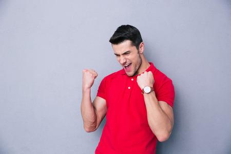 puños cerrados: Hombre que celebra éxito informal sobre fondo gris Foto de archivo