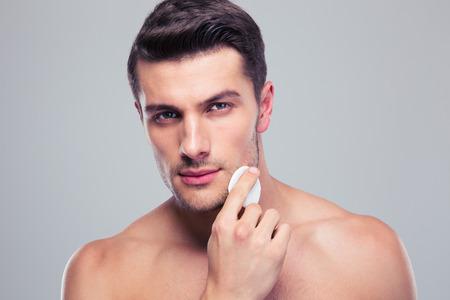 Man nettoyage peau du visage avec des tampons ouate de coton sur fond gris