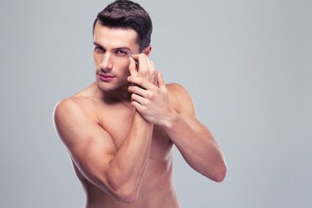 tweezing eyebrow: Handsome man removing eyebrow hairs with tweezing over gray background