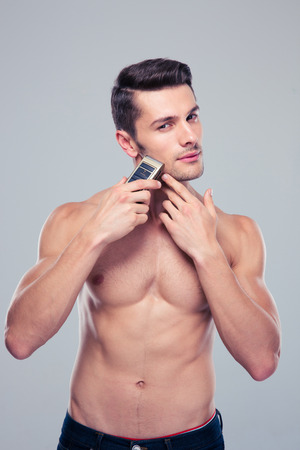 concetrated: Muscular man shaving with electric razor over gray background. Looking at camera