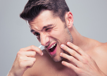 nostril: Man removing nose hair with tweezers over gray background Stock Photo