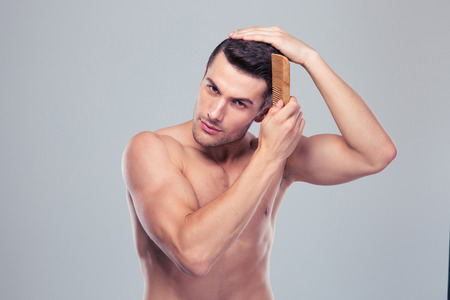 peine: Apuesto joven peinar su cabello sobre fondo gris. Mirando a la cámara